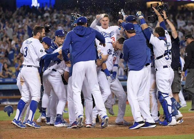 The Dodgers celebrate first baseman Cody Bellinger's walk-off home run in the 10th inning to defeat the Diamondbacks on July 3 at Dodger Stadium.