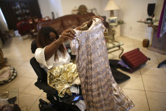 Shawnique Cotton, Ms. Wheelchair Arizona, shows off one of her gowns for the national competition in her home in Mesa, Ariz. on June 30, 2019.