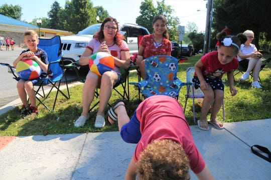 From left to right Cayden Jennings, Tonya Pearson, Jocelyn Pearson and Alyssa Pearson watch as Micah Pearson shows off before the Town of Hyde Park's Independence Day Parade begins on Thursday, July 4, 2019.