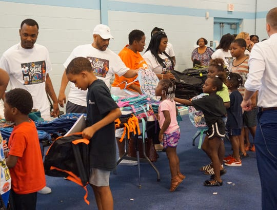 Local football stars Greedy and Lee Lee Williams helped distribute hundreds of backpacks to children Wednesday.