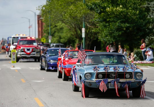 Members of the Greater Ozarks Mustang Team drive down Benton Avenue during the parade.