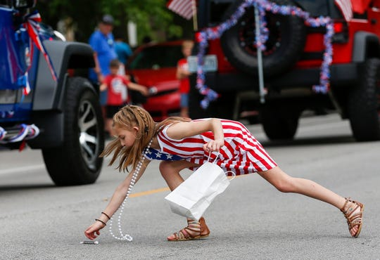 Journey Wildschuetz, 11, reaches for a piece of candy during Springfield's Old Fashioned 4th of July Parade on Thursday, July 4, 2019 in Springfield, Mo.