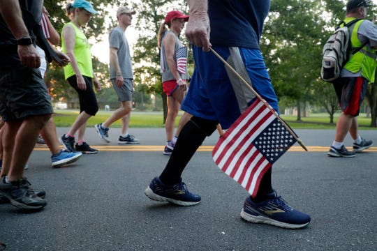 Ernie Andrus, a World War II veteran who is walking across the United States for a second time while in his nineties, carries an American flag as he walks four miles through Monticello, Fla. July 4, 2019.
