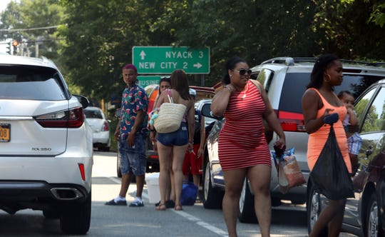 Park-goers return to their car on the side of Route 9W near Rockland Lake State Park July 4, 2019 in Valley Cottage. The park closed after reaching capacity and would admit no more visitors. Clarkstown Police were cracking down on illegally parked vehicles, having them towed.