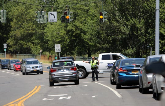 A Clarkstown police officer directs traffic at the south entrance of Rockland Lake State Park in Valley Cottage July 4, 2019. Entry to the park -- a popular spot for those escaping New York City for the holiday -- was shut off at 1:35 p.m. Thursday.
