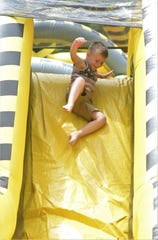 Wyatt Forester goes down the slide at the end of the obstacle course at Stars & Stripes on the River. M&M Party Central offered several inflatable attractions for the event at Zane's Landing Park.