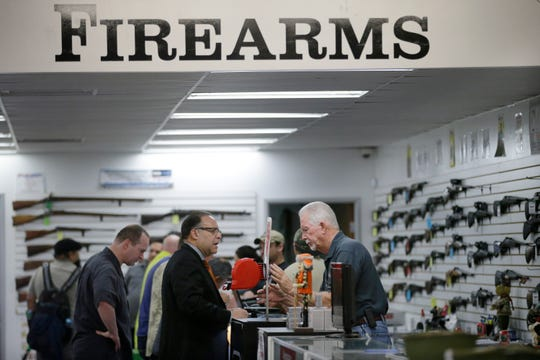 FILE - In this Dec. 9, 2015, file photo, sales associate Mike Conway, right, shows Paul Angulo a pistol at Bullseye Sport gun shop in Riverside, Calif. (AP Photo/Jae C. Hong, File) ORG XMIT: LA309