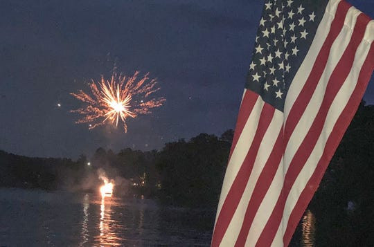 A pontoon boat catches fire on Broadway Lake in Anderson County while fireworks explode over the lake Thursday night.