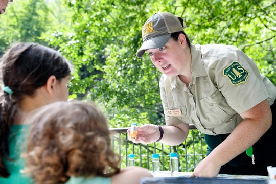 River Ranger Ericka Hincke talks to children about the creatures that live in the rivers of the Pisgah National Forest and how moving rocks can destroy their habitat and food source July 3, 2019.