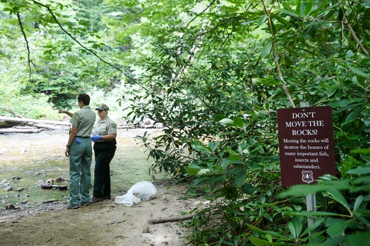 A sign asking visitors to not disrupt the habitat is seen as Mary Allen and Ericka Hincke spot rocks that were moved July 3, 2019 in Pisgah National Forest.