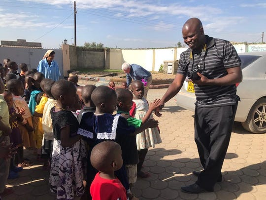 The Rev. Frederick M. Kooro, parochial vicar of St. Thomas Aquinas Church and St. Patrick's Church in Binghamton, greets children who live at Holy Family Children's Home, an orphanage in Nakura, Kenya. Kooro serves as director of the CDN Mission office, which runs the orphanage.