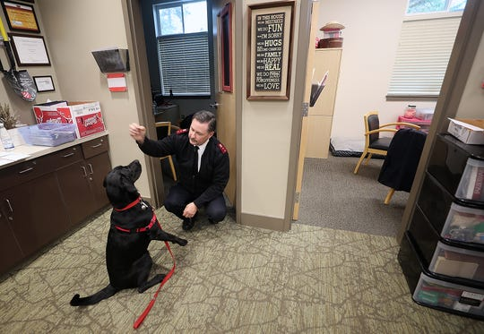 Salvation Army Capt. Lance Walters holds a treat up so his dog Spencer performs a trick as he leaves his office at the Salvation Army in Bremerton on Friday.