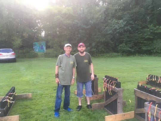 John Logue Jr. (left) of Moorestown and his son John Logue III are shown on July 3 in Barrington, setting up the fireworks display they were about to help fire that night. The pair are carrying on a family tradition.