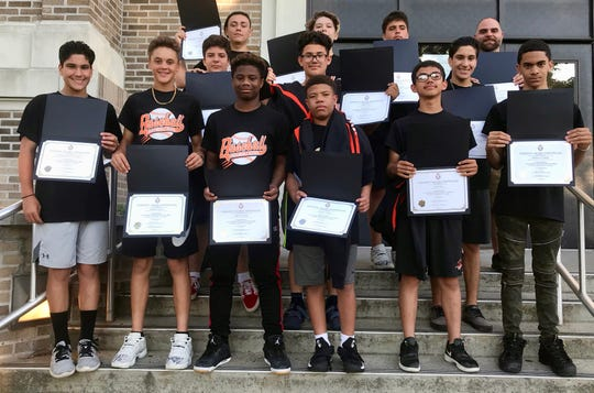 The undefeated Linden middle schools baseball team's players holding up their certificates after being honored by the Board of Education on Thursday, June 27.