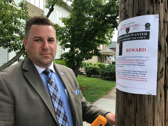 Union County Homicide Task Force Sgt. Andy Dellaquilla installs a poster offering a reward for information in connection with the 2012 fatal shooting of Amber Duncan-Wilson on Friday along Hussa Street. Linden where the homicide occurred.