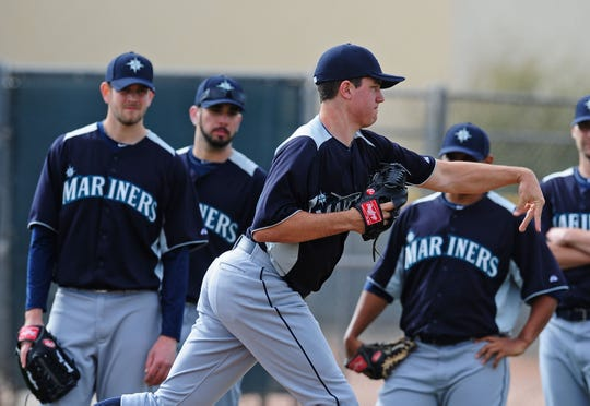 Seattle Mariners pitcher Danny Hultzen throws as teammates look on during a pitchers and catchers workout at the Peoria Sports Complex.