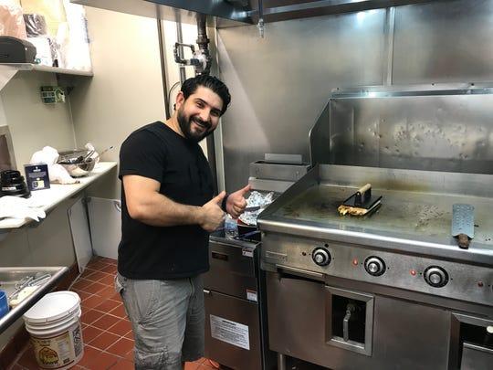 Harith Alkawari, owner of Mr. Falafel, cooks a chicken shawarma sandwich on the flat-top grill.