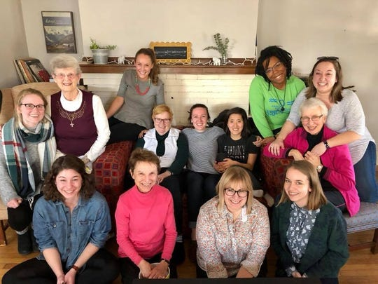 The Sisters and Seekers gather for a potluck at a Grand Rapids home in 2018.  Front row, from left: Natalie Smith, Sister Mary Kay Oosdyke, Tracy Tiemeyer, and Chelsea Smith. Back row, from left: Katie Gordon, Sister Barbara Hansen, Ellie Hutchison, Sister Jarrett deWyse, Kelsey Herbert, Liza Fongers, Kendra Avila, Morgan Bengel, and Sister Lucille Janowiak.