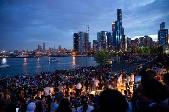 In this Thursday, July 4, 2019 photo, thousands of people gather at Chicago's Navy Pier to celebrate and watch the 4th of July fireworks.  Police said a false report of gunfire set off a stampede that trampled more than a dozen people at Chicago's annual July 4 fireworks display.