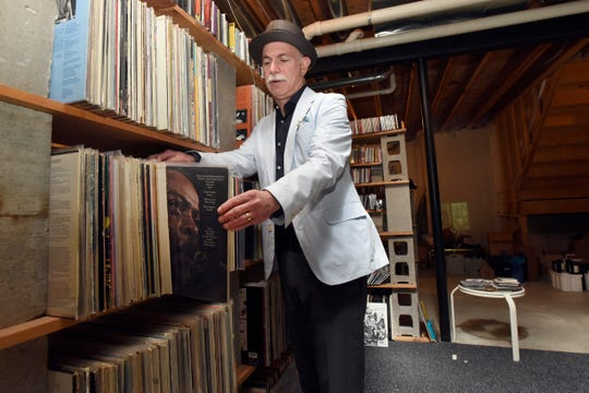 Mark Stryker looks over his large collection of music LPs and CDs, Thursday, June 20, 2019, in Plymouth, Mich.