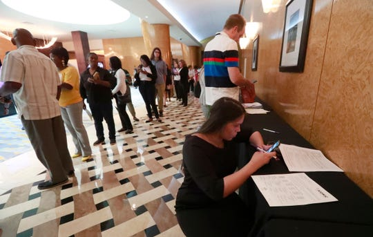 Emily Esparza, lower right, fills out a questionnaire as other job applicants line up at the Seminole Hard Rock Hotel & Casino Hollywood during a job fair in Hollywood, Fla.