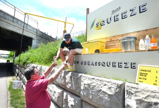 Ray Martin of Saginaw stops his bike ride and gets a lemonade from Eli Wolnerman of Bea's Squeeze along the Dequindre Cut.  Bea's Squeeze, a 650-square-foot parcel,  serving customers along the Dequindre Cut serving lemonade, orange cream and water to joggers, walkers and bikers in Detroit, Michigan on June 8, 2019.
