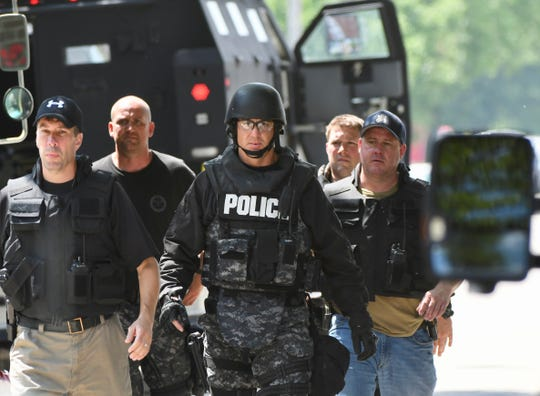 Police wear tactical gear as they deal with a barricaded suspect in St. Clair Shores on Friday, July 5, 2019.