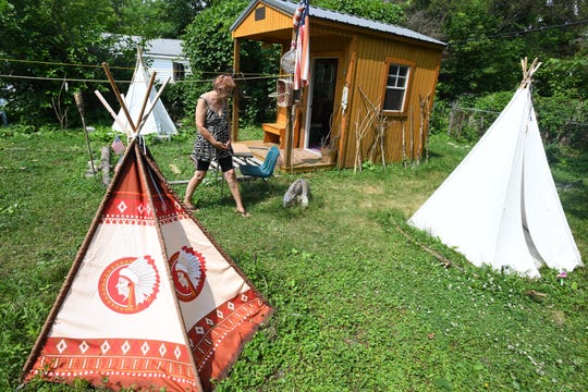 """Mary Pustelak walks through """"The Outpost,"""" a Native American-inspired village she and husband Robert Mounts built in their Detroit backyard."""