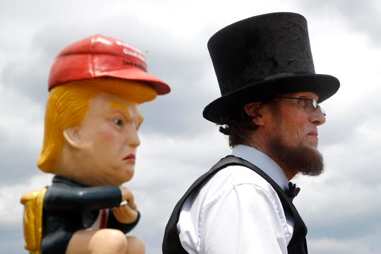 Everett Loud, of Corning, N.Y., and dressed as President Abraham Lincoln, stands near a sculpture of President Donald Trump holding a cell phone while sitting on a toilet before Independence Day celebrations, Thursday.