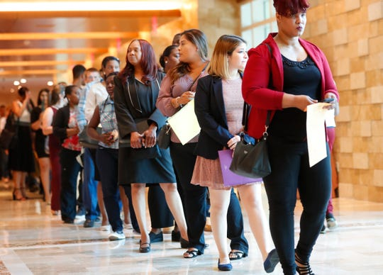 Applicants line up at the Seminole Hard Rock Hotel & Casino Hollywood during a job fair in Hollywood, Fla.