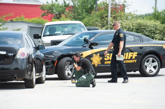 Law enforcement personnel work behind Long John Silver's on White Horse Road after one person died after a shooting at a Walmart in Berea Friday, July 5, 2019.