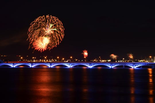 Fireworks from the 15th Street Bridge with the blue, 10th Street Bridge lights in the foreground