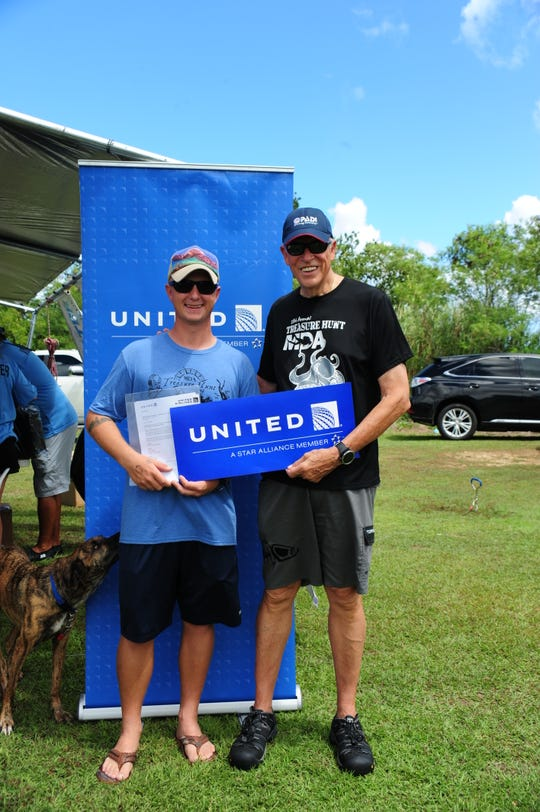 Joshua M. Butenhoff, left, was awarded a round-trip ticket to anywhere in Micronesia by Micronesian Divers Association President Lee Webber at the 29th Annual MDA Treasure Hunt that was held at the Agat Cemetery Dive channel on June 22, 2019.