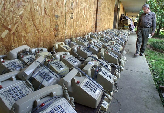 Donald Travis of Jackson strolls past telephones stacked outside the boarded windows of the Sun-n-Sand Hotel in October 2001 before the beginning of an auction to liquidate the contents of the landmark business which closed its doors for good. Travis is a member of the Jackson Central Lions Club which had met in the Sun-n-Sand for the last several years.