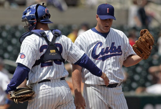 In this May 9, 2007 photo from the Des Moines (Iowa) Register, Iowa catcher Koyie Hill heads back to the plate as Ben Howard takes the mound in the 5th inning. Howard got the win. Howard retired from pro baseball in 2008.