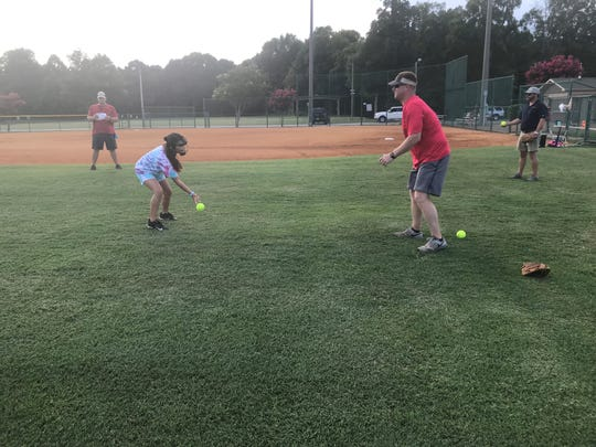Ben Howard goes through defensive drills helping girls from the Madison Central 8-year-old all-star softball team work on fielding grounders during practice on July 1 at West Jackson Baptist Church.