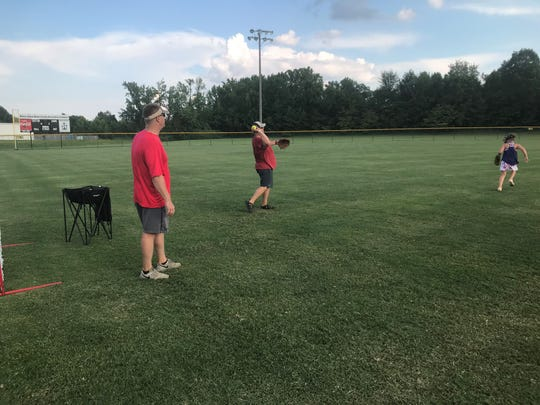 Ben Howard watches and helps instruct players on running after fly balls as Josh Allen, another coach on the Madison Central 8-year-old all-star softball team, throws balls for them to catch.