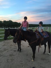 Kellie Harper rides her horse, Shera, while her son Jackson rides her other horse, Phoenix.