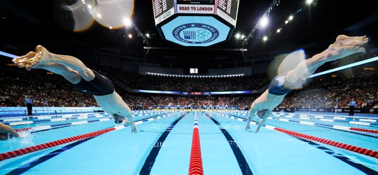Davis Tarwater, left, and Michael Phelps dive at the start of men's 100-meter butterfly semifinal at the U.S. Olympic swimming trials, Saturday, June 30, 2012, in Omaha, Neb. (AP Photo/Mark J. Terrill)