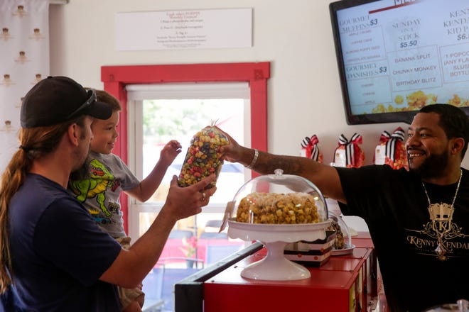 Kenny Johnson, right, hands Rhyder Johnson, 4, and his uncle, Brandon Slaughterbeck their popcorn bag at Kenny Kendall's Gourmet Popcorn, 295 Dayton road, Friday, July 5, 2019 in Dayton.