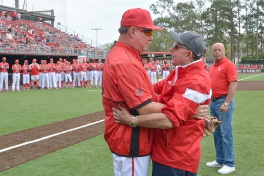 "UL coach Tony Robichaux, left, who died Wednesday, embraces his father, Ray Robichaux, after receiving a pitch from him before a game at renovated M.L. ""Tigue"" Moore Field at Russo Park in 2017 ."