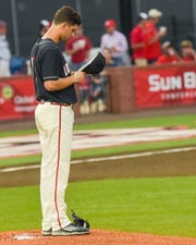 Former UL pitcher Gunner Leger, shown here praying before a game in 2018, is mourning the death of Ragin' Cajuns coach Tony Robichaux.