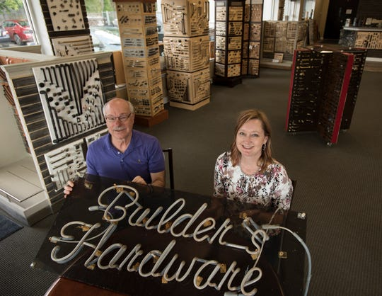 Ron Knapp, the former owner of Builders Hardware, and daughter Caryn Drenth, who recently purchased the business, pictured Wednesday, July 3, 2019, with the original neon sign from the East Lansing location.
