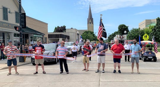 Manitowoc Mayor Justin Nickels (center) cuts the ribbon on the inaugural Manitowoc Fourth of July parade.