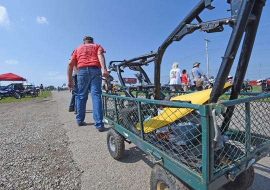 A bargain hunter hauls away his purchase of a motorcycle frame Friday at the swap meet at the Mid-Ohio Sports Car Course.