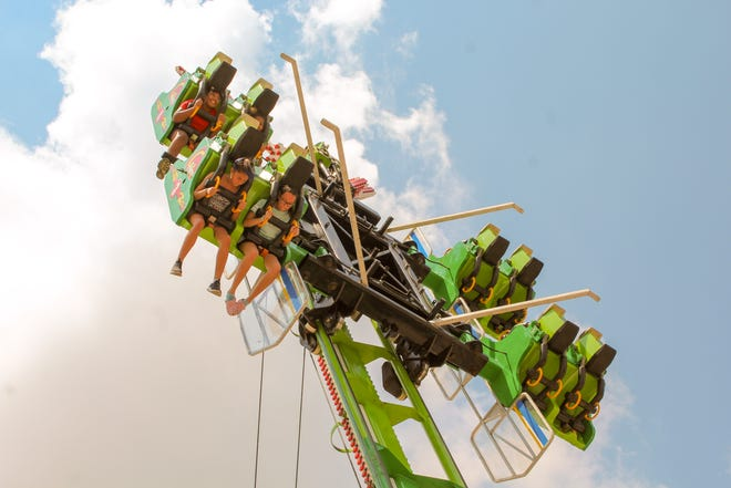 A group of people on a rollercoaster at the Marion County Fair.