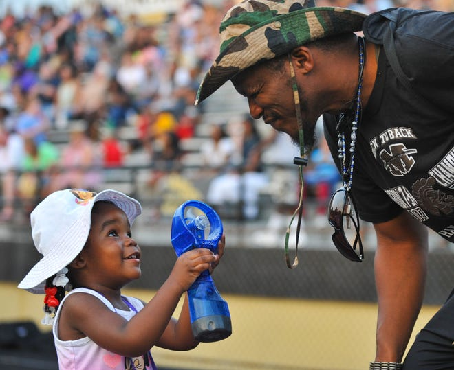 Fri Aug 23, 2013 - Aaryon Hudson, 3, cools her dad Aaron off with a spray bottle as Millington Central High School hosted the Germantown Red Devils Friday night. Warm temperatures and high humidity greeted the fans and athletes as the high school football season officially kicked off Friday night.