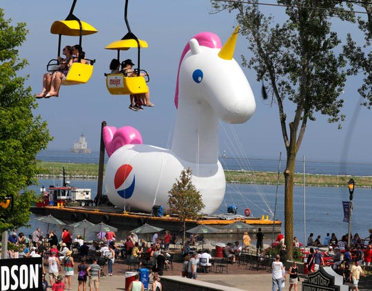 A 60-foot unicorn towers over the crowds at Summerfest Friday. The inflatable mythical creature moved into the Summerfest Lagoon was part of a Pepsi promotion.