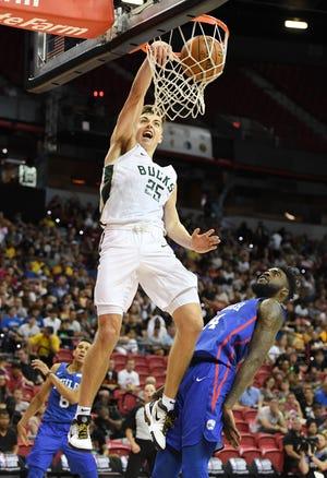 The Bucks' Daulton Hommes dunks in front of 76ers' Norvel Pelle on Friday.