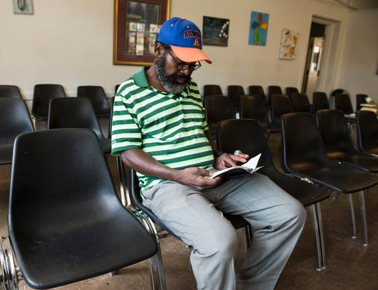 Robert Smith reads his prayer book at the First Baptist Caring Center in Montgomery, Ala., on Tuesday, July 2, 2019.